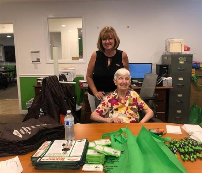 Two females in a office with SERVPRO bags and pens