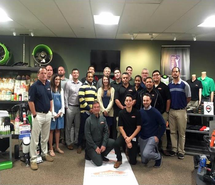 A large group of people in a room with SERVPRO equipment