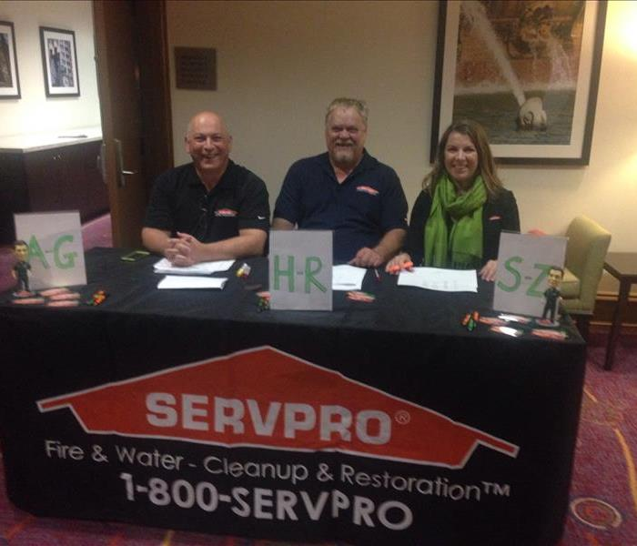 Three people sitting at a table with a SERVPRO banner covering the table